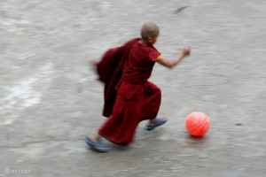 Free tibetan buddhist monk kicking a ball